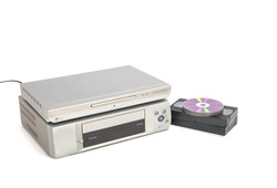 Dvd player over vhs player next to video tapes and cds isolated on white background. Image of appliances horizontally with copy space.