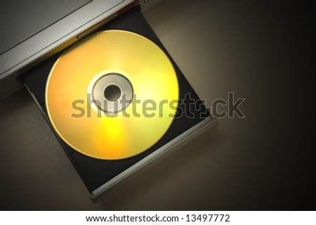 dvd player with open tray with a gold disk with dramatic light