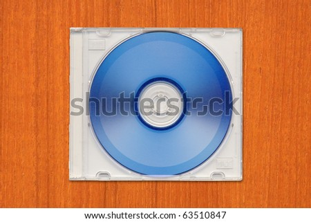 DVD-R in semi clear plastic case on wooden table.