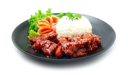 Dwaegangjeong Fried Pork with Spicy and Sweet Sauce Sprinkle Sesame Served Rice Traditional Korean Food Crispy pork Style on Black Plate Decorate Vegetables sideview