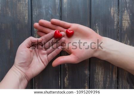 Dwie pary rak na drewnianym tle. W rekach trzymaja dwa malutkie czerwone serduszka. Happy family. Top view, copy space.  Zdjęcia stock ©
