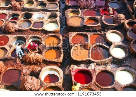 Dye reservoirs and vats in traditional tannery of city of Fez, Morocco, with men working in the dye vats (viewed from from a Terrace) #1191073453