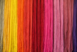 dyed colored yarn hanging on wall in bunches forming a rainbow pattern. Background of Colorful Yarn. Colorful yarns for embroidering.