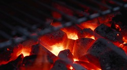 Dying and flying embers, glowing briquettes. Barbecue in the garden, close-up of embers.