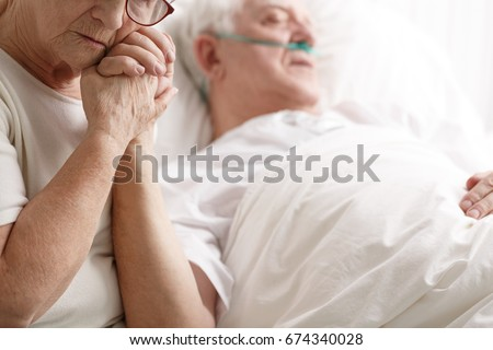 Dying senior man in hospital bed and his sad wife holding his hand Stock foto ©