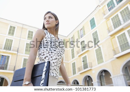 Dynamic businesswoman walking through a European city's square, turning back. - stock photo