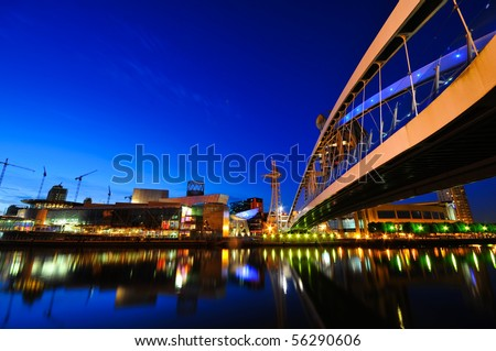 Dynamic Futuristic Cityscape at night with colourful lights reflected in the water
