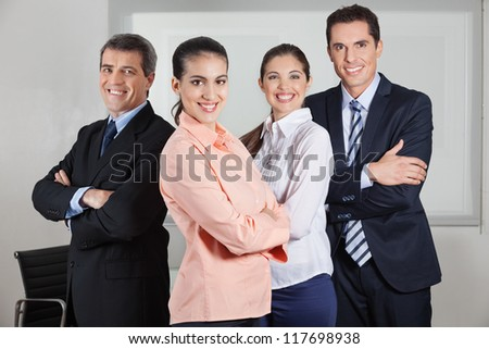 Dynamic happy busines team standing in the office with the arms crossed