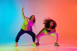 Dynamic lifestyle. Two beautiful girls dancing hip-hop on colorful gradient background in neon lights. Concept of movement and active lifestyle. Youth culture, style, fashion, hobby, ad