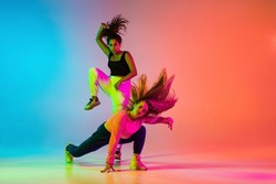 Dynamic lifestyle. Two beautiful hip-hop dancers in motion on gradient blue orange backlground in neon. Sport achievement, expression. Concept of dance, youth, hobby, dynamics, movement, action, ad