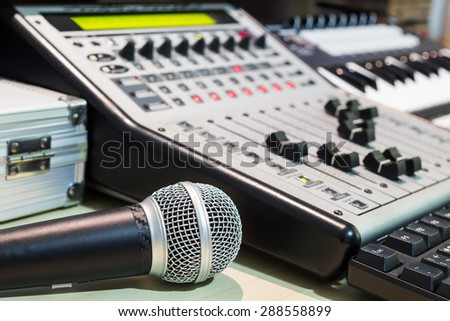dynamic microphone, digital studio mixer & keyboard synthesizer, focus to mic for music recording, radio / tv broadcasting  background