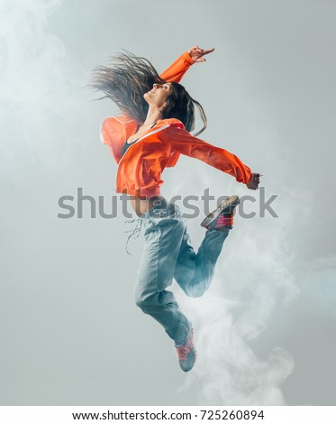 Dynamic modern style performer jumping and dancing: vitality, happiness and fitness concept