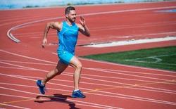 Dynamic movement of male runner on running track, run.
