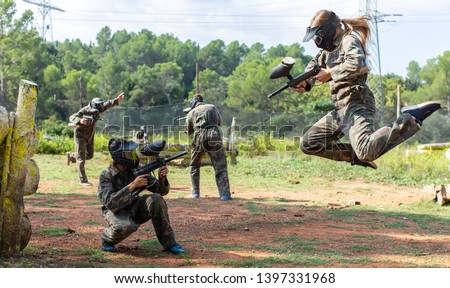 Dynamic paintball battle. Portrait female player jumping and aiming marker on member of opposing team