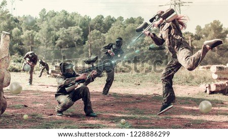 Dynamic paintball battle. Portrait female player jumping and aiming marker on player of opposing team