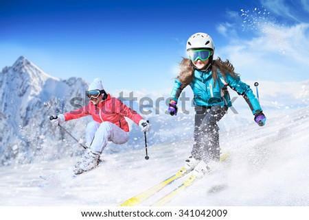 Dynamic picture of a skier and snowboarder on the piste in Alps