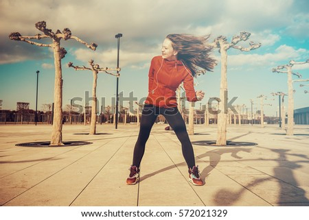 Dynamic street outdoor workout,jumping dancing active woman ready to new day.Morning exercises #572021329