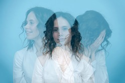 Dynamic triple exposure portrait of a woman, facing three different directions,and having different emotions, from sad to happy. Over blue background.