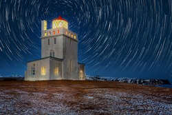 Dyrholaey lighthouse under star trails. The light station at Dyrholaey was established in 1910, near the village Vik, on the southern tip of Iceland.