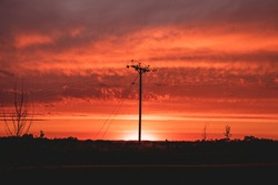 Dystopian, orange hellish sky with isolated power line, depicting global warming, pollution, and the damaging effects of burning fossil fuels for electricity to our environment.