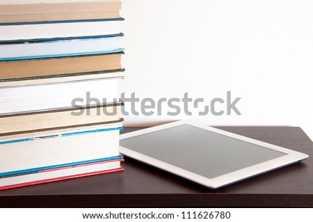 E-book reader and stack of books on a table
