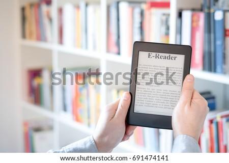E-book reader in hands in a bookstore