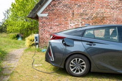 e car at charging station in front of a rural house