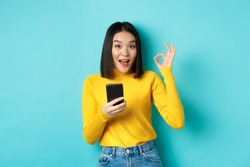 E-commerce and online shopping concept. Portrait of asian woman showing OK sign and using mobile phone, recommend application, standing over blue background