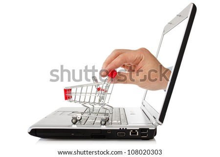e-commerce concept. hand reaches out of a laptop with a shopping cart