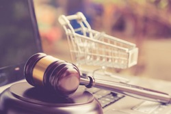 E-commerce law, rules and regulations concept : Wooden judge gavel and shopping cart on a laptop, depicts good practice vendor must do for consumer e.g provide clear data, order cancellation, refund