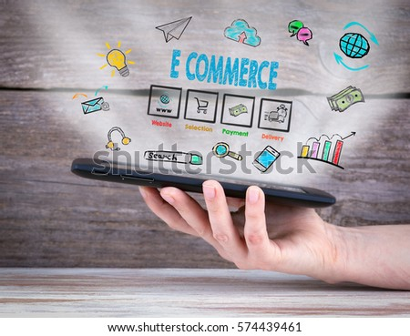 E commerce. Tablet computer in the hand. Old wooden background