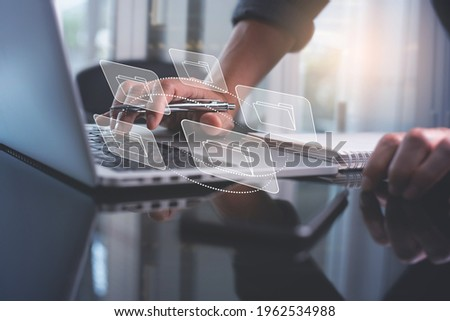 E-document, paperless office concept. Businessman working on laptop computer keyboard with electronics document icons on virtual screen