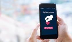 e-donation concept.close-up of man hands make an online donate via mobile phone