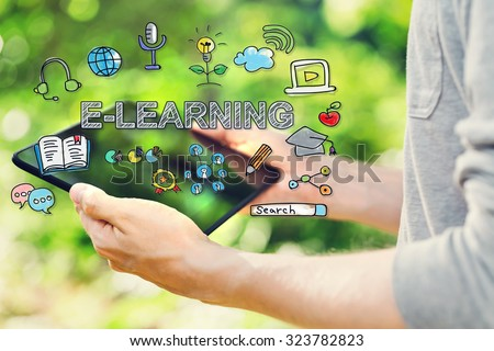 E-Learning concept with young man holding his tablet computer outside in the park  #323782823