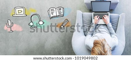 E-Learning with man using a laptop in a modern gray chair #1019049802