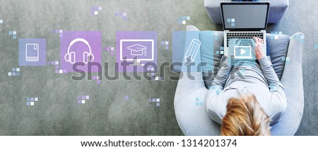 E-Learning with man using a laptop in a modern gray chair Stock photo ©