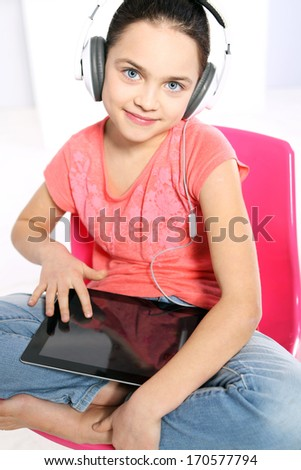 E-learning  / Young girl in a pink shirt with earphones and a tablet