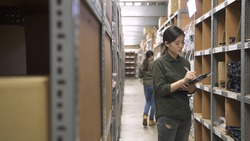 e-shop female employee counting cardboard boxes on shelf and writing on clipboards in warehouse. beautiful women coworkers working together in stockroom doing stock taking. colleague wear uniform