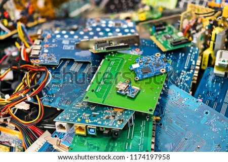 E-waste heap from discarded laptop parts. Connectors, PCB, notebook cards. Colorful blurry background from PC components. Idea of electronics industry, eco, sorting and disposal of electronic waste.