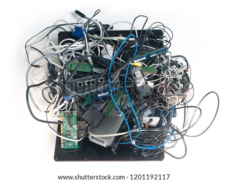 E-waste mess. A jumbled up pile of old wires cables, power adapters, circuit boards, laptop computer, cell phones isolated on White. Forming a mass of tech spaghetti.