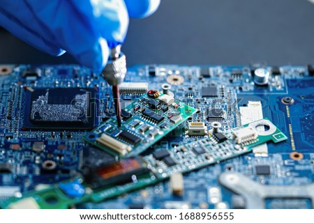 E-waste, technician repairing inside of hard disk by soldering iron. Integrated Circuit. the concept of data, hardware, technician and technology.