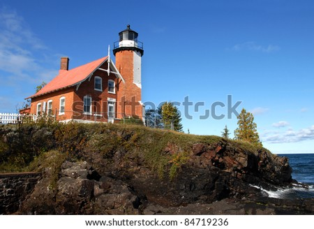 Eagle Harbor Lighthouse is perched on a rocky cliff above Lake Superior.  House and light are of the same brick architeture and joined as one.