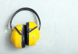 Ear hearing protection. Yellow working protective headphones noise muffs, toolwork in construction site