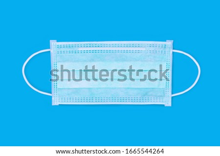 Ear-loop face mask 3 ply, Safety masks on blue background. dust protection respirator and breathing medical respiratory mask.