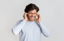 Ear pain concept. Man grimaces and touches ears, free space