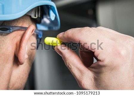 Ear Plugs Hearing Protection Simple Solutions. Factory Worker in Blue Hard Hat Preparing To Use Foamy Plug. #1095179213