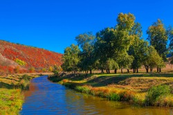 early autumn scenery with little river and hill