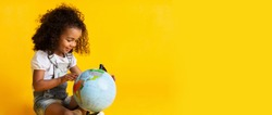 Early education. Little girl pointing to world globe, yellow background, copy space