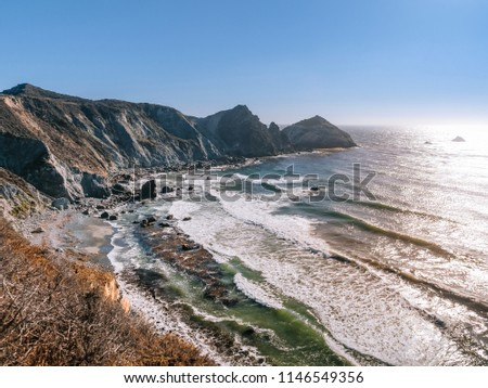 Early evening at Willow Creek Beach near Big Sur, California. View from the popular vista point off Cabrillo Highway along the Pacific Coast. Clear blue skies with bright sun reflection on the water.
