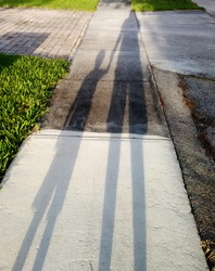 Early evening shadows of a father and son out for a walk